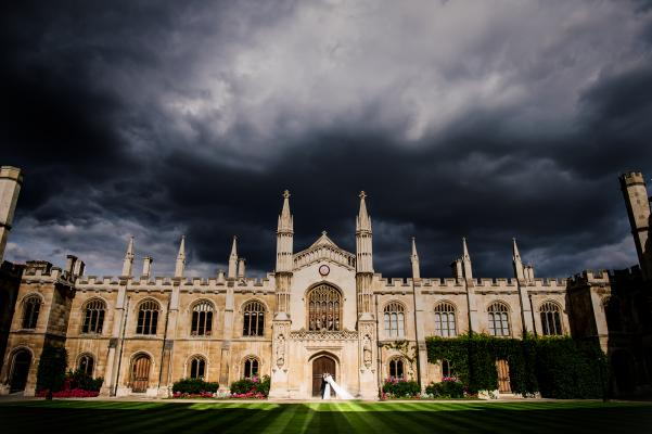Bride & groom, and a stormy sky over the Chapel | Photo credit : Alex Beckett Photography