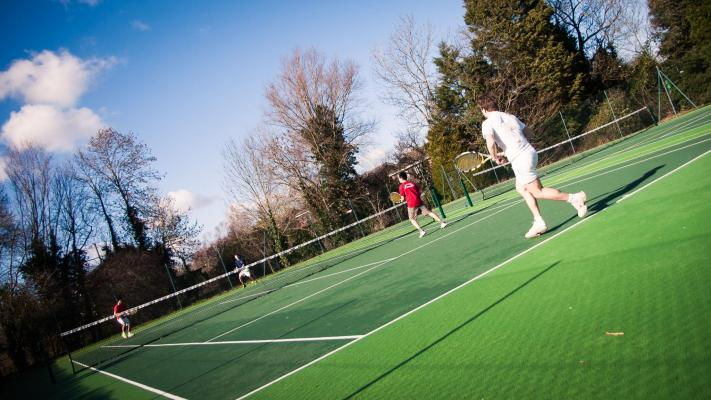 Students playing tennis in the College tennis courts next to Leckhampton